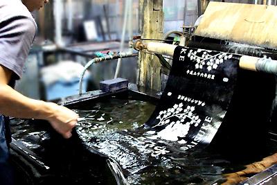 染めた後はすぐに真水で洗い、生地の両面にブラシをかけ糊を落とします。